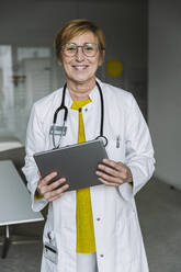 Portrait of smiling doctor holding tablet - MFF05552