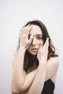 Portrait of depressed young woman with hands on her face - FVSF00057