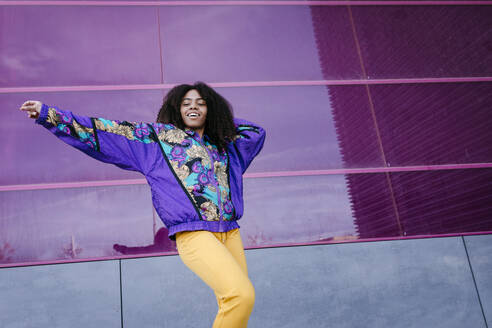 Young woman with urban look dancing, pink glass wall in the background - TCEF00468
