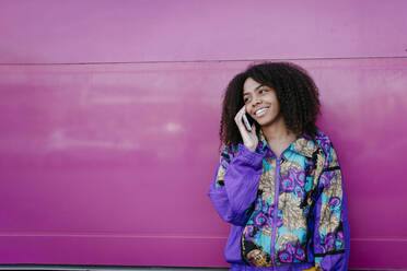 Smiling woman talking on the phone, pink wall in the background - TCEF00471