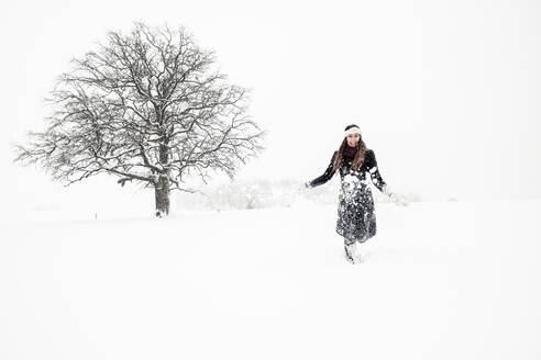 Happy young woman throwing snow in winter landscape - WFF00307
