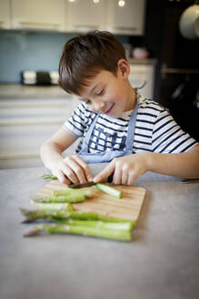 Portrait of smiling little boy cutting green asparagus in the kitchen - HMEF00867