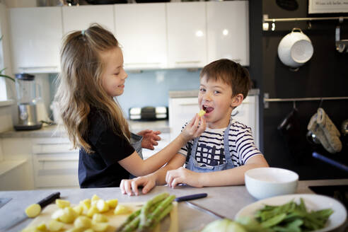 Girl feeding her little brother with potatoes in the kitchen - HMEF00870