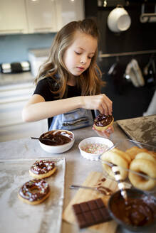 Portrait of girl decorating home-baked doughnuts with sugar granules - HMEF00873