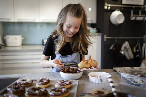 Portrait of smiling girl garnishing home-baked pastry with chocolate icing - HMEF00876