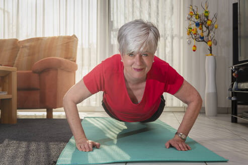 Happy senior woman doing pushup at home - FRF00911