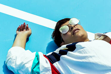 Portrait of woman wearing mirrored sunglasses and lying on ground - ERRF03410