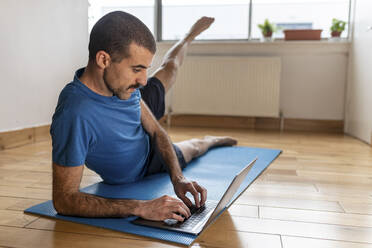 Sportive man lifting his leg and using laptop at home - WPEF02759