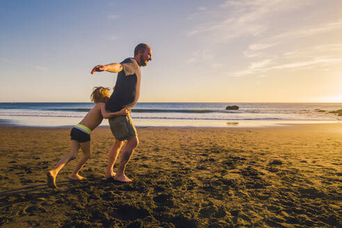 Father and son playing and running on the beach - IHF00325