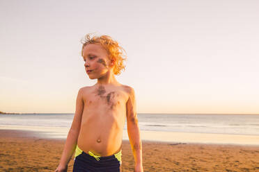 Portrait of a little boy on the beach, with mud in his face - IHF00328