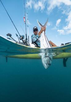 Split shot of man in a kayak catching a fish - AMUF00039