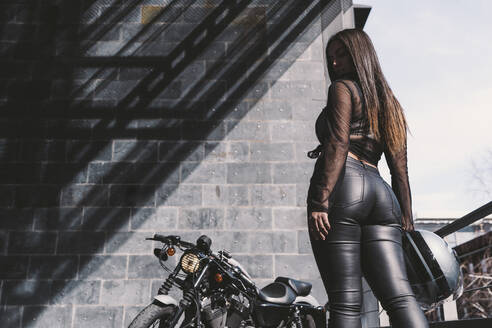 Sexy young woman holding motorcycle helmet, standing by her motor bike, rear view - DAMF00339