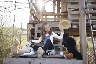 Girl playing with her teddy bears at tree house - HMEF00880