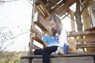 Girl sitting in garden at tree house and writing something in her blue diary - HMEF00883