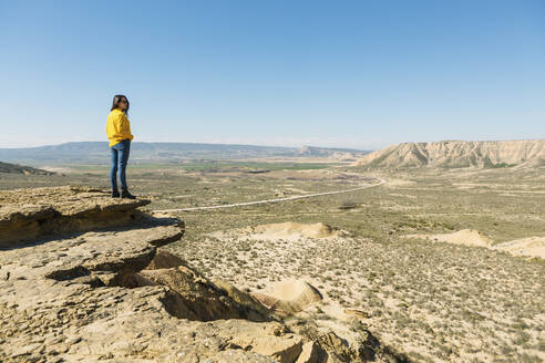 Woman enjoying the view in desertic landscape of Bardenas Reales, Arguedas, Navarra, Spain - XLGF00012