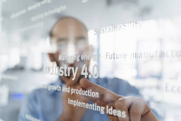 Businessman in front of glass pane pointing on words, industry 4.0 - DIGF09630