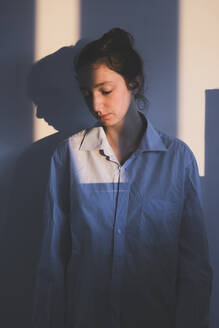 Portrait of sad woman looking down during sunrise at home - FVSF00096