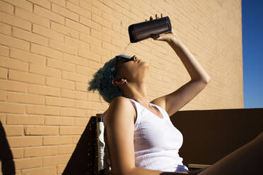 Young woman with blue hair pouring water over her head on balcony - ERRF03424