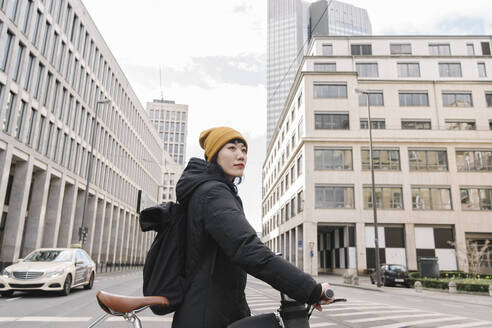 Woman with bicycle in the city, Frankfurt, Germany - AHSF02208