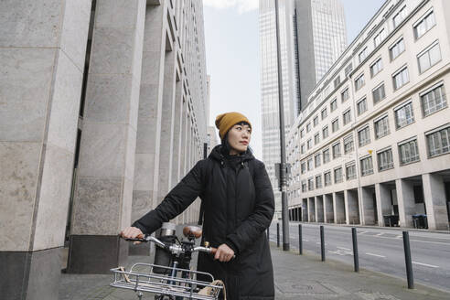 Woman with bicycle in the city, Frankfurt, Germany - AHSF02211