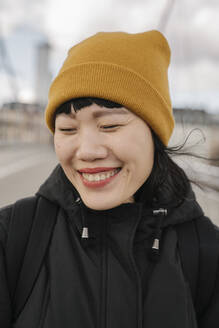 Portrait of happy woman with closed eyes on a bridge - AHSF02235