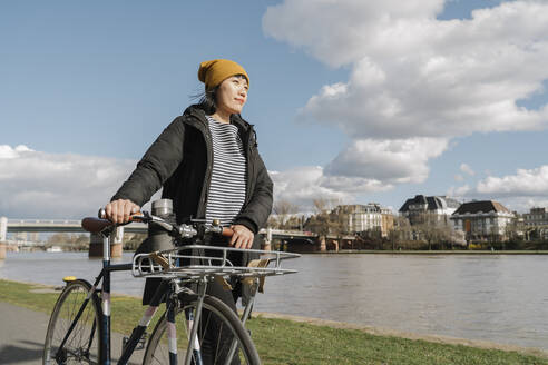 Woman with bicycle on the riverbank, Frankfurt, Germany - AHSF02250