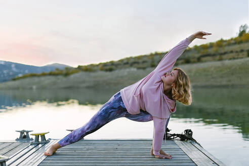 Young woman doing yoga on a jetty, triangle pose - AGGF00001