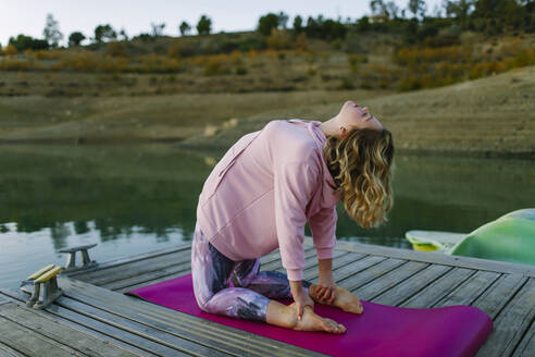 Young woman doing yoga on a jetty, camel pose - AGGF00004