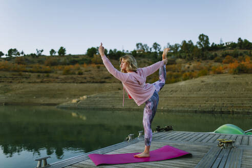 Young woman doing yoga on a jetty, dancer position - AGGF00007