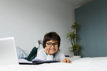 Portrait of relaxed little boy lying on bed with laptop doing homework - VABF02774