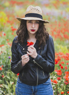 Portrait of young woman with red lips standing in poppy field - FVSF00100