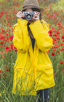 Young woman wearing yellow rain coat photographing on flower meadow with poppies - FVSF00103