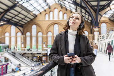 Woman at train station with headphones and mobile phone, London, UK - WPEF02777