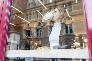Businesswoman having a coffee break at a cafe in the city - WPEF02780