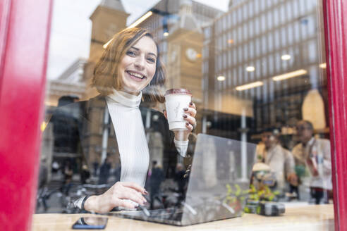 Portrait of happy businesswoman using laptop at a cafe in the city - WPEF02786