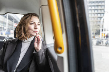 Woman in the rear of a taxi looking out of the window, London, UK - WPEF02792