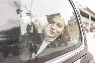 Woman in the rear of a taxi looking out of the window, London, UK - WPEF02795