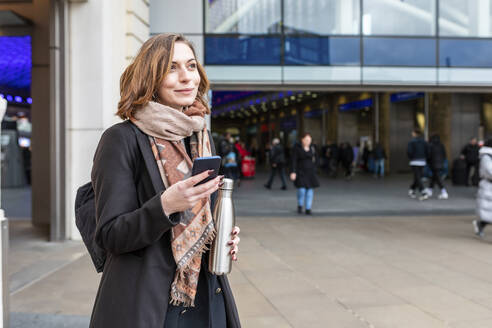 Portrait of woman with mobile phone in front of train station, London, UK - WPEF02801
