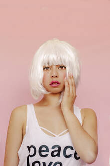 Portrait of young woman wearing white wig in front of pink background - ERRF03433