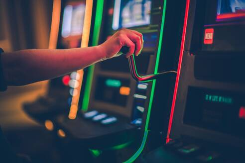 Cropped Hand Of Boy Playing Games On Slot Machine - EYF03893