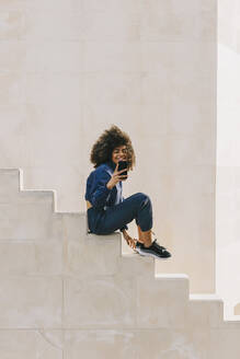 Stylish young woman wearing tracksuit and using cell phone on stairs - AGGF00020