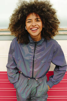 Portrait of happy stylish young woman wearing tracksuit outdoors - AGGF00035