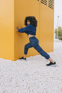 Stylish young woman doing stretching exercise at a yellow wall - AGGF00038