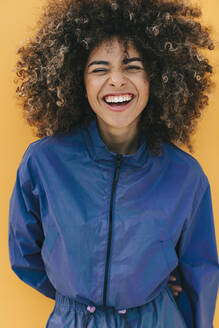 Portrait of happy stylish young woman wearing tracksuit outdoors - AGGF00041