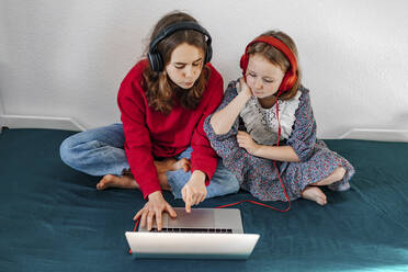 Portrait of two sisters with headphones sitting on bed looking at laptop - OGF00268
