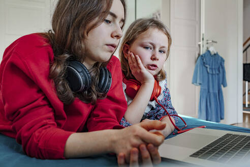 Portrait of two sisters with headphones and laptop on bed - OGF00271