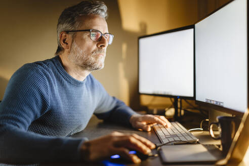 Mature man sitting at desk at home working on computer - MCVF00297