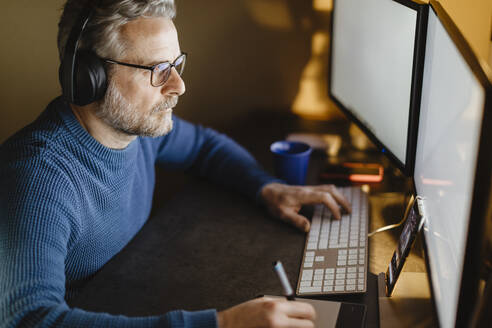 Mature man with headphones sitting at desk at home working with graphics tablet and computer - MCVF00300