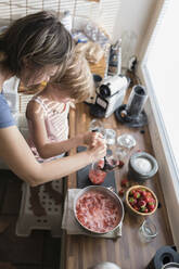 Mother and little daughter preparing strawberry jam in the kitchen at home - PSIF00377