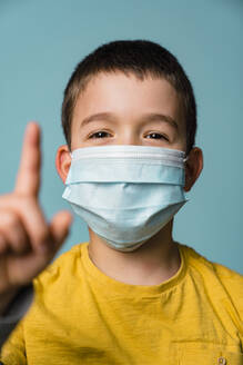 Portrait of boy with mask wagging finger - MGIF00897